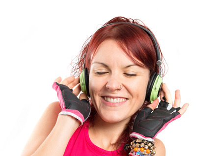 Young sport girl listening music over white background Stock Photo - 24983018