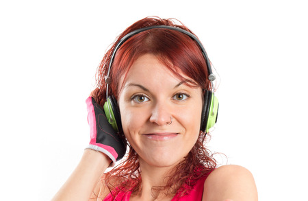 Young sport girl listening music over white background  photo