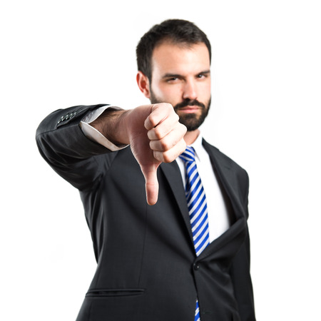 Young businessman with his thumb down over white background  Stock Photo