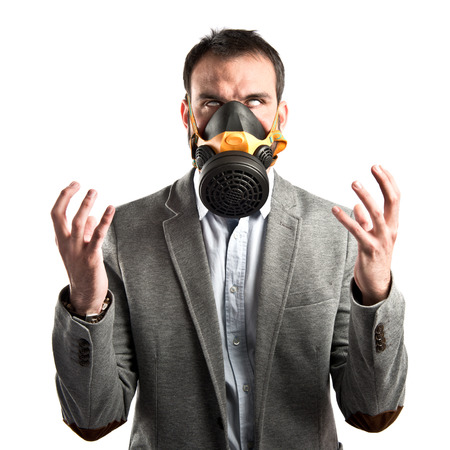 young businessman with gas mask over white background  photo