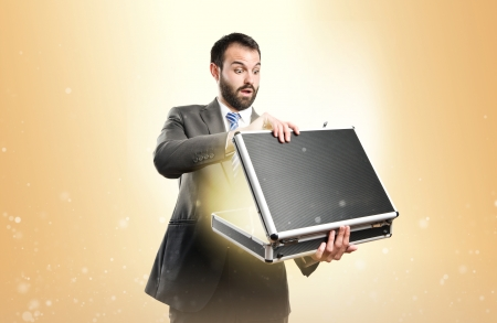Young businessman open his briefcase over ocher background