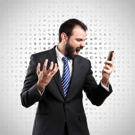 Young businessmen shouting to mobile over grey background.  photo
