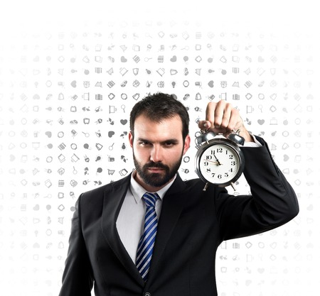 Young businessman holding an antique clock over white background  photo