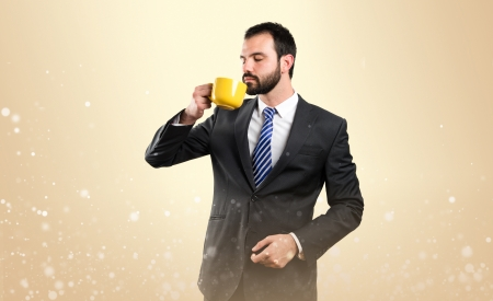 Young businessman drinking a coffee over ocher background  photo