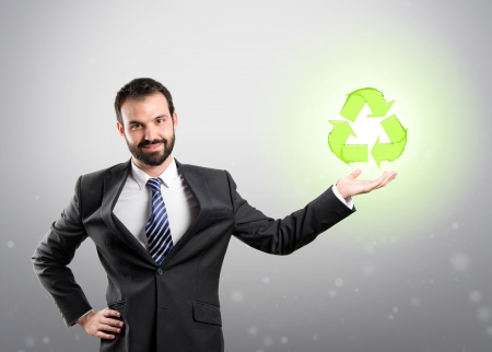 Businessman holding a recycling icon over grey background  photo
