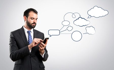 Business man sending a message over grey background.  photo