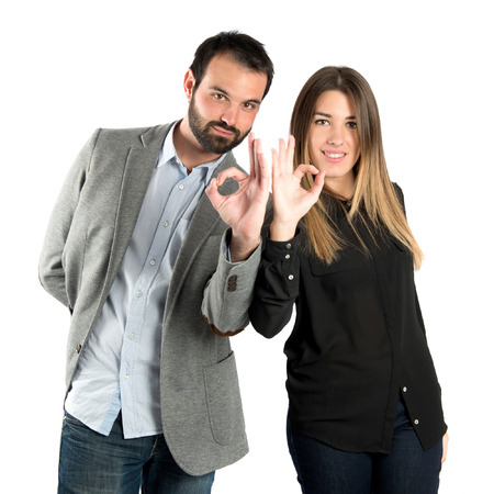Couple making Ok sign over white   photo