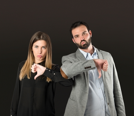 Couple with their thumbs down over black background  photo