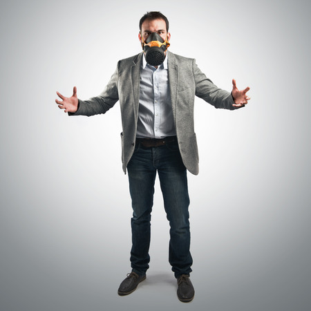 young businessman with gas mask over grey background  photo