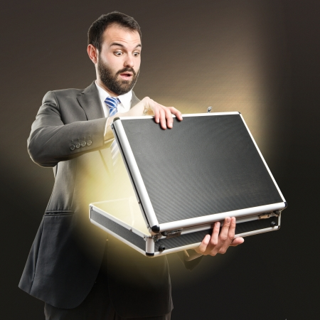 Young businessman open his briefcase over dark background  photo
