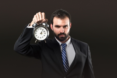 Young businessman holding an antique clock over black background  photo