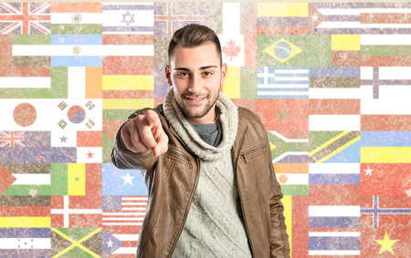 Young man pointing over background with flags  photo