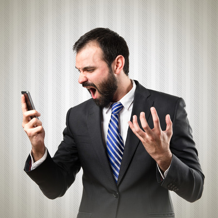 Young businessmen shouting to mobile over textured grey background.  photo