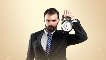 Young businessman holding an antique clock over ocher background Stock Photo - 26243835