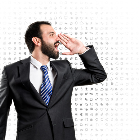 Young businessman screaming over background with icons  photo