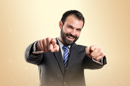 Businessman pointing to the front over ocher background  photo