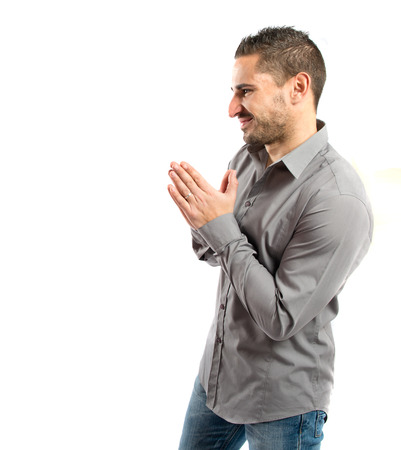 supplication: Handsome man pleading over isolated white background
