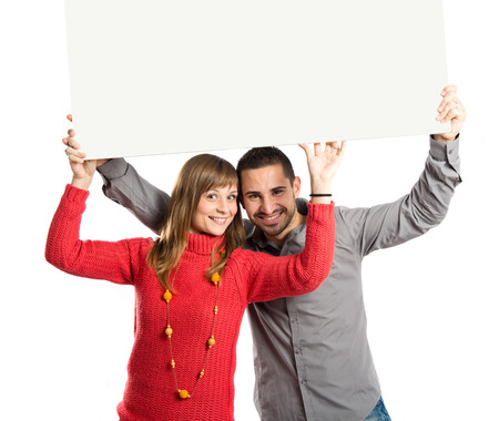 Couple holding placard over white background photo