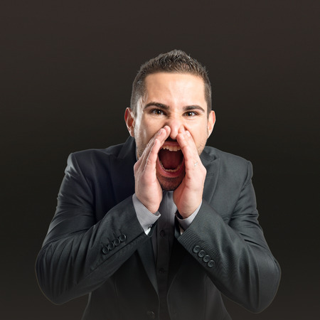 Businessman angry and shouting over black background  photo