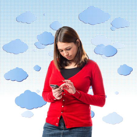 miniskirt: Young girl sending a message with her mobile over background with clouds. Stock Photo