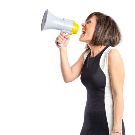 Pretty girl shouting with a megaphone over white  photo