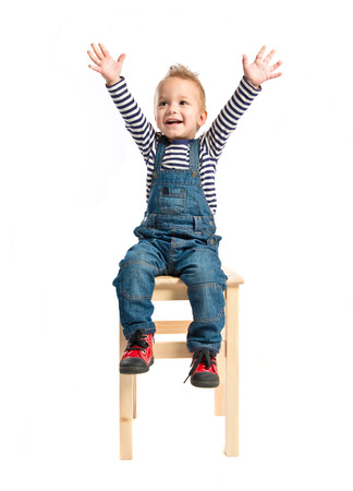 Kid sitting on a wooden chair over white background  photo