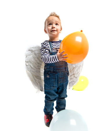 Cute kid with wings and balloon over white background  photo