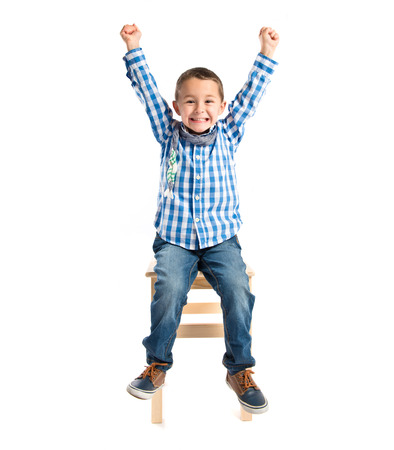 blond boy: Lucky boy on a wooden chair over white background