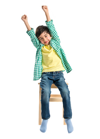 Lucky boy on a wooden chair over white background  photo