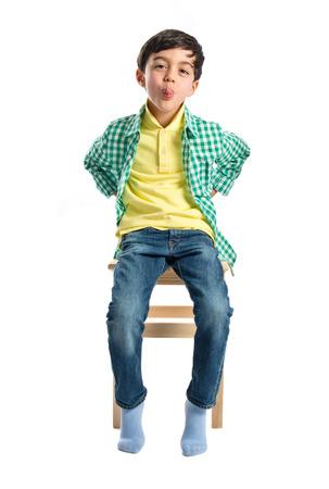 mockery: Boy making a mockery on wooden chair over white