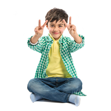 Boy making a victory sign on wooden chair over white background  photo