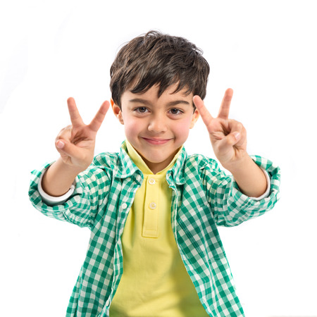 Boy making a victory sign over white background  photo