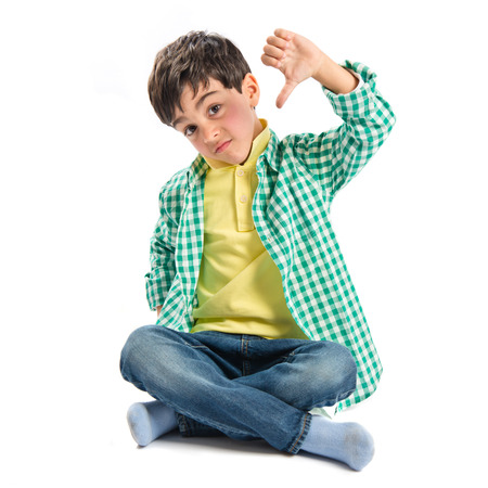 Kid making bad sign over white background  photo