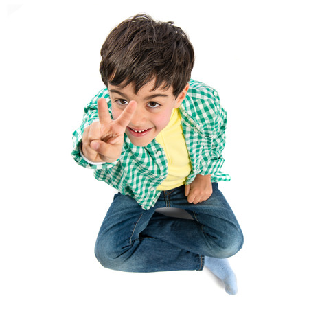 Cute kid making victory gesture over white background  photo