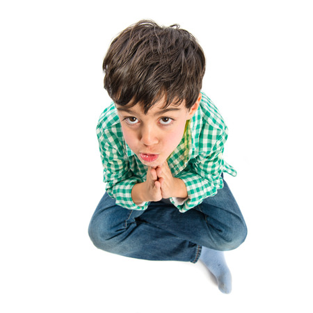 supplication: Brunette boy pleading over isolated white background