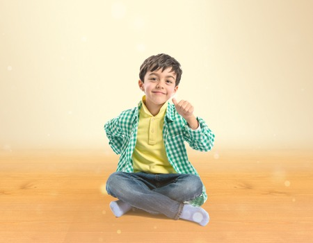 Boy making a OK sign over ocher background  photo