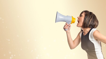Pretty girl shouting with a megaphone over ocher background  photo