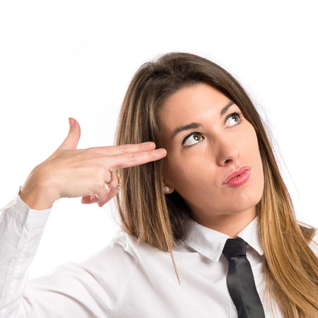 Young businesswoman making suicide gesture over white background  photo