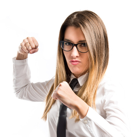 Young businesswoman giving punch over isolated white background  photo