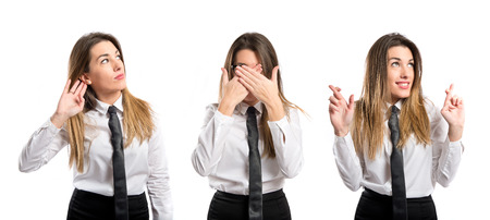 young businesswoman covering her eyes, listening, and crossing her fingers photo