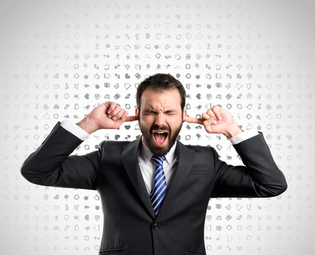 business man covering her ears over icon background Reklamní fotografie - 28443065