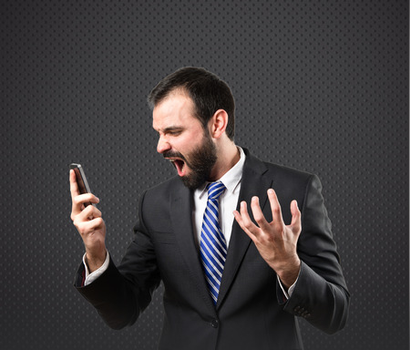 Young businessmen shouting to mobile over black background.  photo