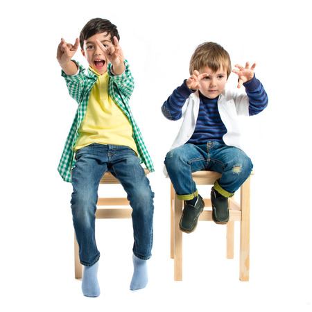 insult: Kids doing the horn sign over white background  Stock Photo