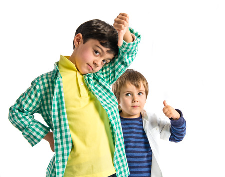 Kids making good and bad sign over white background  photo
