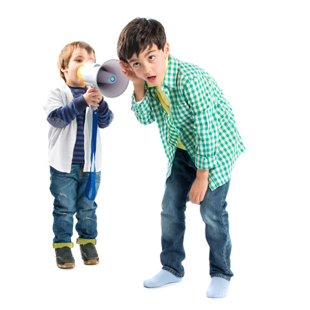 Kid shouting at his friend by megaphone over white background  photo