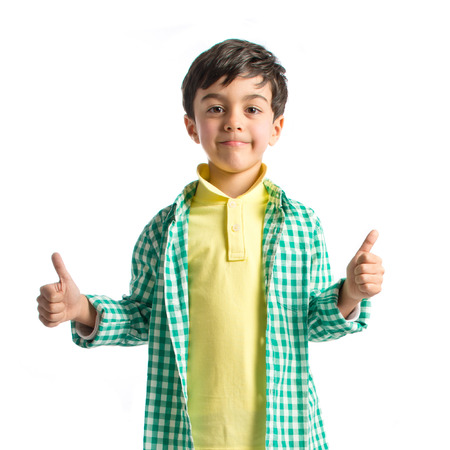 Boy making a OK sign on wooden chair over white background  photo