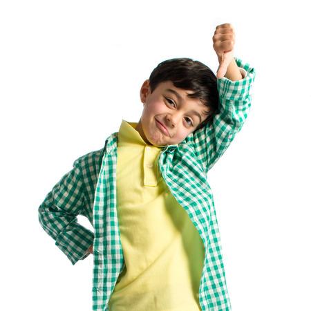 Kid making bad sign over white background  photo