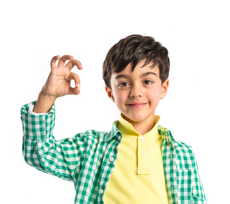 Boy making a OK sign over white background  photo
