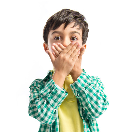Kid covering his mouth over white background