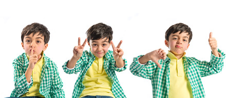 Kid doing silence gesture, victory sign and good-bad gesture photo